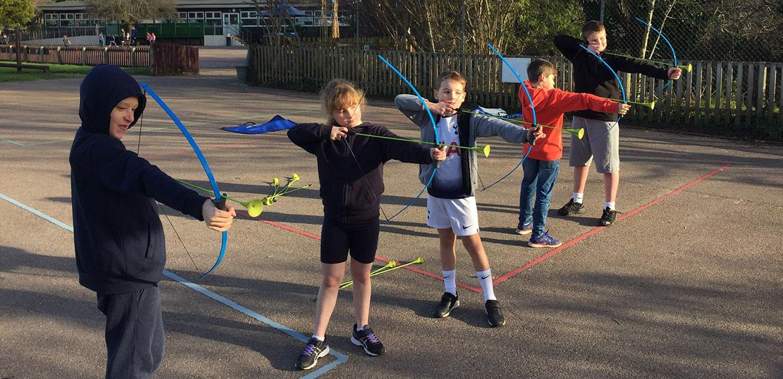 Kids doing archery on holiday camp